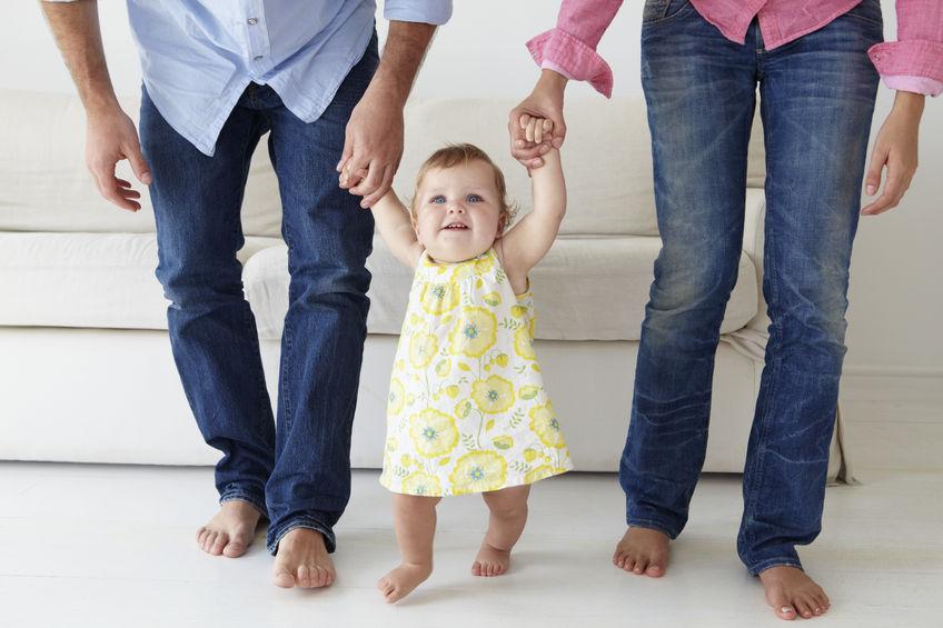 33551906 - padres enseñando a una niña a caminar